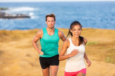 Fit run people couple jogging for fitness running on beach landscape nature outdoors. Woman and man sports athletes training cross-country trail running. Team partners, Asian woman, Caucasian man. Stock Photo