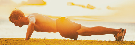 Fitness man working out arms doing push-ups outside in sunset. Fit body male athlete workout outdoor full length panoramic banner.