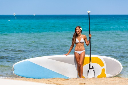 Paddleboard SUP Asian athlete woman showing SUP paddleboarding board and paddle in Hawaii beach. Fitness sport lifestyle. Beach rental equipment on travel vacation. Bikini Chinese multiracial woman.