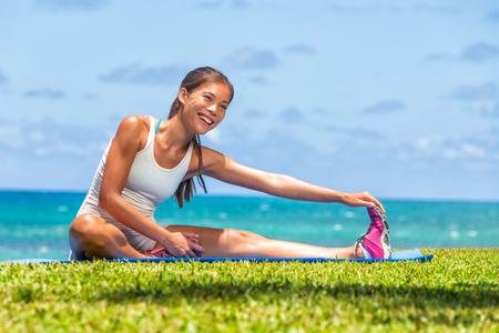 Mujer fitness estirar las piernas haciendo calentamiento antes de ejecutar el entrenamiento de entrenamiento al aire libre. Atleta asiático estirando los músculos isquiotibiales laterales yoga estira la pierna estira ejercicios en el gimnasio al aire libre. Foto de archivo