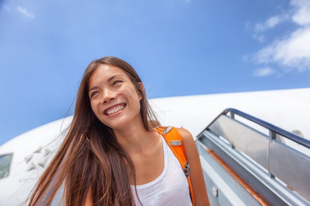 Airport travel plane arrival girl tourist arriving at destination walking out of airplane on tarmac. Happy Asian passenger woman student with backpack after plane landing at summer vacation. 版權商用圖片