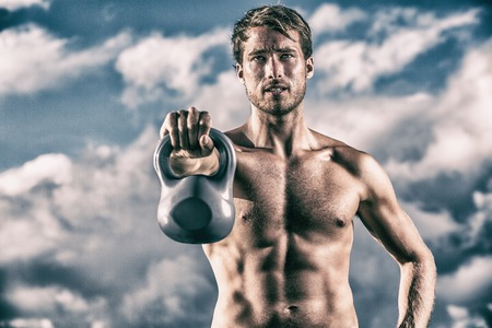 Fit man training lifting kettlebell weight bodybuilding with muscular chest and abs. Topless fitness model weightlifting.