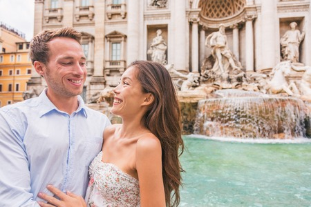 Rome couple on romantic date by Trevi Fountain in Roma, Italy. Romantic luxury honeymoon Europe cruise travel tourists lovers traveling in european city. Asian woman falling in love with Italian man