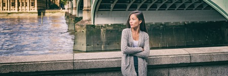 City lifestyle young Asian woman taking a break on city street of London relaxing by the Thames River by Big Ben, UK, Europe. Banner panoramic background of cityscape.