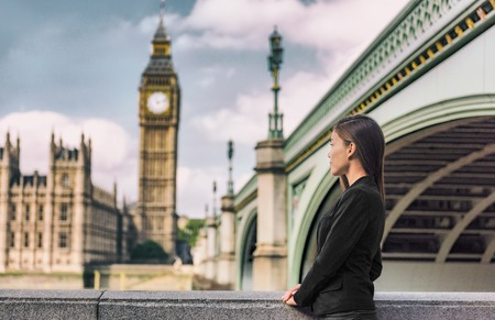 London business people city lifestyle young businesswoman looking at Parliament Big Ben clock tower, UK. Europe politics solicitor or realtor, woman wearing formal black suit for career life.