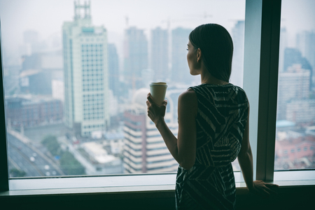 Businesswoman drinking coffee at work contemplative looking out the window of high rise skyscraper building during morning tea break. Stress, mental health in the workplace. Career job concept.