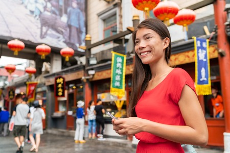 China food market tourist woman walking using phone on Beijing hutong street travel vacation adventure. City lifestyle young Asian girl. Asia summer travel destination. Girl traveling Asia chinatown.