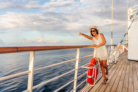 Happy cruise vacation fun travel woman pointing watching whales or wildlife sighting from deck of boat on Europe summer destination cruising vacation holiday. Luxury relaxation getaway. Stock Photo