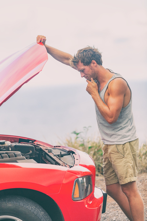 Car breakdown problem. Road trip travel young man on side of the road with broken engine looking at motor in open hood repairing issue.