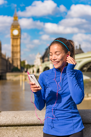 London lifestyle woman runner listening to music on smart phone near Big Ben. Female running girl resting after training in city. Fitness girl smiling happy on Westminster Bridge, London, England, UK. Фото со стока