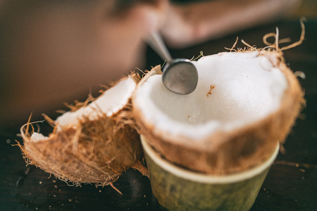 Fresh coconut being open and eaten in restaurant. Woman using spoon to remove meat from coco to eat fresh. Tropical food.