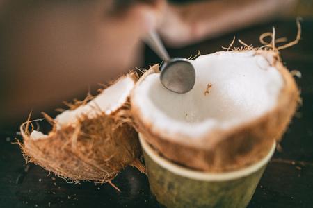 Noix de coco fraîche ouverte et mangée au restaurant. Femme à l'aide d'une cuillère pour retirer la viande de coco pour manger frais. Nourriture tropicale. Banque d'images