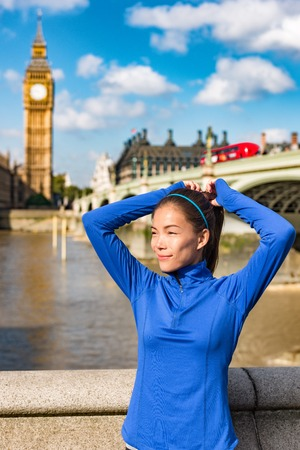 London fitness sport athlete getting ready for run workout tying hair into ponytail with headband and hair ties at Big Ben westminster travel destination. UK marathon training.