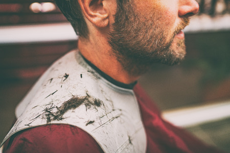 Freshly cut hair fallen on shoulders of man getting haircut at barbershop. Closeup of short brown hair haircut on hair cutting cape.