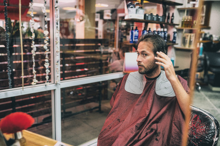 Haircut hair salon man looking in mirror at his hairstyle after barber cut with scissors touching placing his hair. Male beauty men care lifestyle.