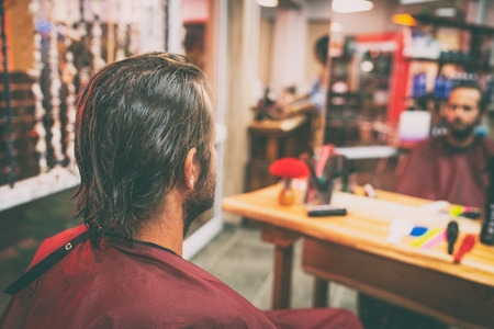 Hair salon man getting haircut or coloring of long brown hair. Portrait from behind of male customer with wet hair and cutting cape ready for hairstyle. 写真素材