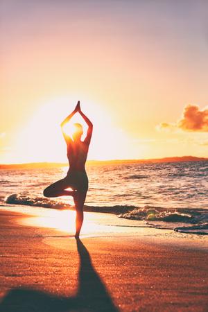 Yoga-Wellness-Retreat-Klasse auf morgendlicher Sonnenaufgangsstrandlandschaft. Schattenbild des Mädchens, das im vertikalen Hintergrund der Baumhaltungsmeditation steht.