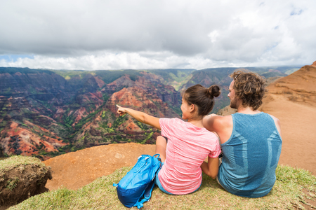 Gente que va de excursión en los excursionistas de Hawaii que apuntan a Kauai. feliz excursionista pareja estilo de vida saludable al aire libre mirando la vista del cañón de Waimea. Pareja joven descansando sentado en la naturaleza en Kauai, Hawaii, USA.