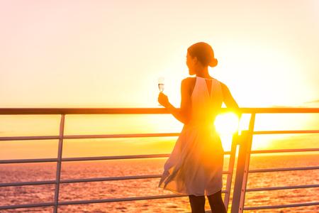 Luxus-Kreuzfahrtschiff reisen elegante Frau, die ein Glas Champagner trinkt und den Sonnenuntergang vom Bootsdeck über dem Ozean in Europa im Urlaub genießt. Kreuzfahrt in den Urlaub segeln.
