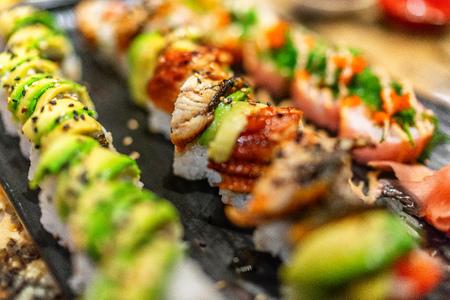 Sushi-Rollen im Restaurant. Luxuriöse Sushis mit Avocado- und Aal-Topping, Rainbow Maki, Thunfisch, Tobiko, Sesam. Japanisches Essen. Standard-Bild