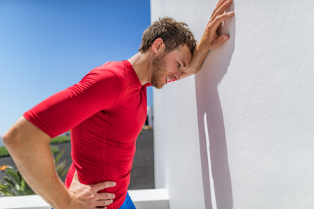 Tired athlete runner man exhausted leaning on wall of fatigue breathing hard after difficult exercise. Fitness person sweating of sun stroke, migraine, heat exhaustion muscle back pain or cramps. Stock Photo