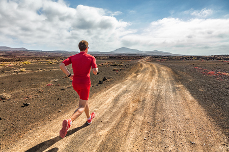 Läuferathlet, der im Bergpfad läuft. Fit Mann Training Cardio im Freien. Sommersport-Fitnesslauf in Wüstenlandschaft.