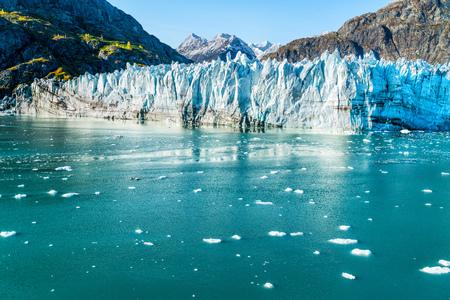 Viaggio di vacanza di crociera dell'Alaska di Glacier Bay. Il riscaldamento globale e il concetto di cambiamento climatico con lo scioglimento del ghiaccio. Barca da crociera verso il paesaggio del ghiacciaio Johns Hopkins e le montagne della gamma di Mount Fairweather.