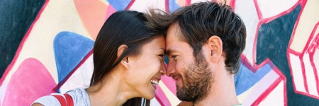 Young couple in love laughing together at Berlin wall, Germany, Europe travel. Portrait of happy multiracial people, Asian woman, Caucasian man kissing. Banner panorama on graffit background. Stock Photo