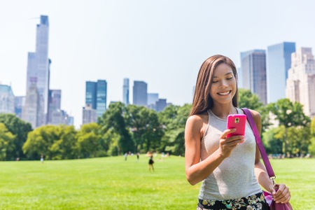 Happy Asian woman texting sms on mobile phone in New york City, NYC. Young girl walking in Central Park meadow in Manhattan. Фото со стока