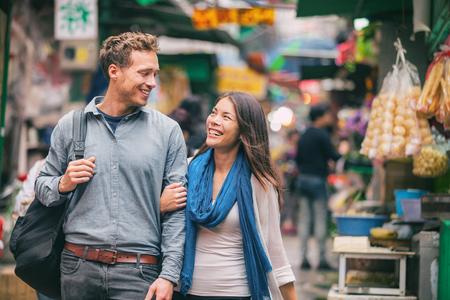 Paar wandelen winkelen in chinatown markt in Hong Kong, China. Gelukkige toeristen in reizen kijken naar straatvoedselverkopers die lachen en samen genieten van cultureel avontuur. Stockfoto