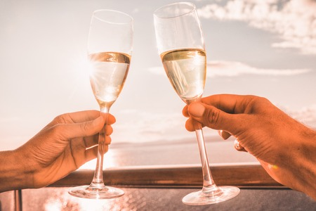 Luxury cruise ship travel couple toasting champagne glasses for celebration honeymoon. Caribbean holiday drinking doing cheers at sunset view sun flare of cruise holiday destination. Фото со стока