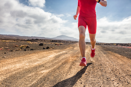 Trail runner athlete man running on dirt mountain path in red compression clothes outfit and running shoes for extreme terrain. Stock fotó