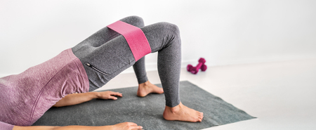 Fitness woman training on yoga mat with resistance workout exercise bands glute bridge with hip abduction at home. Fit girl training with circle hoop booty band for thighs exercising banner panorama. Reklamní fotografie