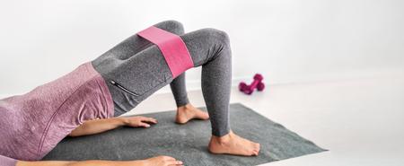 Mujer fitness entrenamiento en colchoneta de yoga con bandas de ejercicios de resistencia puente de glúteos con abducción de cadera en casa. Ajuste la formación de la muchacha con la banda del botín del aro del círculo para los muslos que ejercitan el panorama de la bandera.
