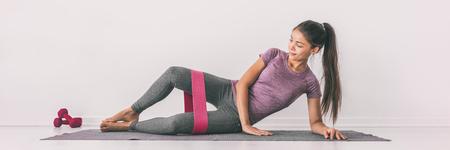 Ejercicio de concha de banda de resistencia en forma de piernas de entrenamiento de niña en demostración de tapete. Entrenamiento de abductores de cadera para quemar calorías. Foto de archivo
