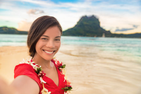 Luxury vacation selfie happy woman smiling taking photo with mobile phone on Bora bora island cruise travel destination at sunset. Smiling gorgeous Asian girl wearing Tahiti flower lei for luau.