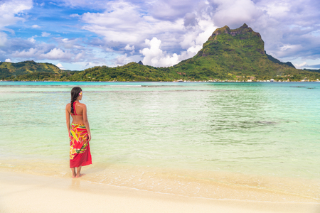 Tahiti voyage de luxe plage vacances femme marchant en jupe de plage polynésienne sur une île paradisiaque idyllique en Polynésie française. Tenue traditionnelle rouge, bikini et fille de fleur.