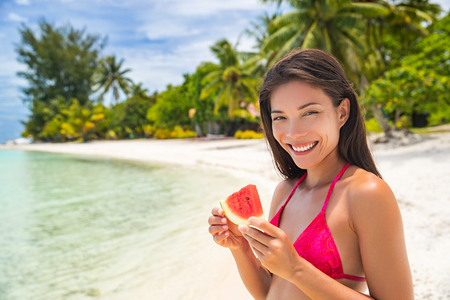Beach summer lifestyle happy girl eating fresh watermelon fruit slice enjoying tropical vacation in the sun. Asian woman relaxing tanning on exotic holiday.