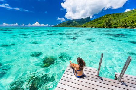 Bora Bora Luxusreise über Wasser Bungalow Resort Urlaub Bikini Frau im Tahiti Hotel. Tropisches exotisches Reiseziel. Mädchen entspannendes Sitzen auf privatem Balkon unter der Sonne mit Blick auf das Meer.