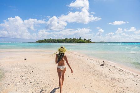 Beach paradise bikini woman enjoying tropical getaway vacation in Rangiroa atoll, Tuamotu islands, French Polynesia.