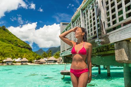 Luxury hotel outdoor shower bikini woman washing hair rinsing body after ocean swim at overwater bungalow villa. Tahiti travel destination resort lifestyle vacation in paradise. Stock Photo