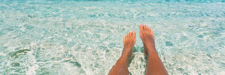 Relax feet beach vacation summer banner background - Woman relaxing on tropical travel destination swimming in blue water panorama. Banco de Imagens