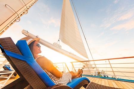 Luxus-Kreuzfahrt-Urlaubsfrau, die sich im Liegestuhl entspannt und den Sonnenuntergang auf dem Yachtdeck mit Segel im Windsegeln im Sommerreiseleben des Urlaubsziels genießt. Standard-Bild