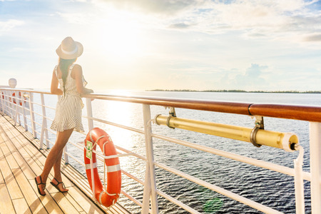 Luxury cruise ship travel elegant tourist woman watching sunset on balcony deck of Europe mediterranean cruising destination. Summer vacation cruiseship sailing away on holiday. Stock Photo