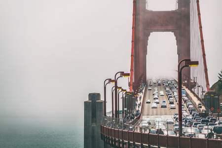 San Francisco Golden Gate Bridge in fog background . Traffic, cars commuters people urban lifestyle scene.