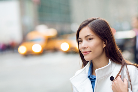 New Yorker woman walking on New York City street waiting for car lift rideshare taxi. Asian young professional with yellow taxi cabs cars traffic in background. Biracial person. Stock Photo