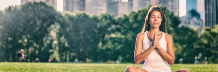 Yoga woman meditation praying outside in city park wellness banner panorama .Summer exercise lifestyle active young Asian girl meditating background. Stock Photo