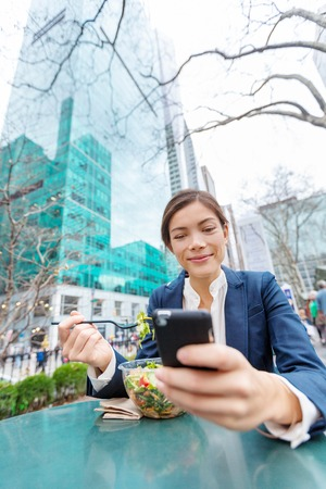 Businesswoman eating salad on lunch break in park. Young professional Asian business woman using phone online data for texting in New York City, USA. Biracial lady Asian Chinese  Caucasian.