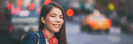 People city lifestyle young happy Asian woman walking in New York City street urban background with red headphones. Panoramic banner header.