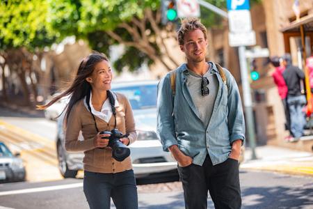 Jóvenes estudiantes pareja turistas caminando en las calles de la ciudad tomando fotos con la cámara en viajes. Mujer asiática, hombre caucásico amigos estilo de vida urbano casual.